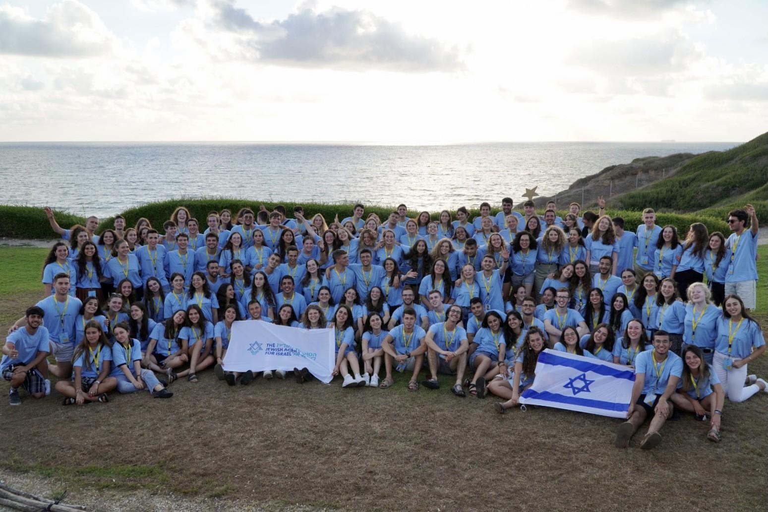 שליחים צעירים בתמונה קבוצתית על רקע הים התיכון