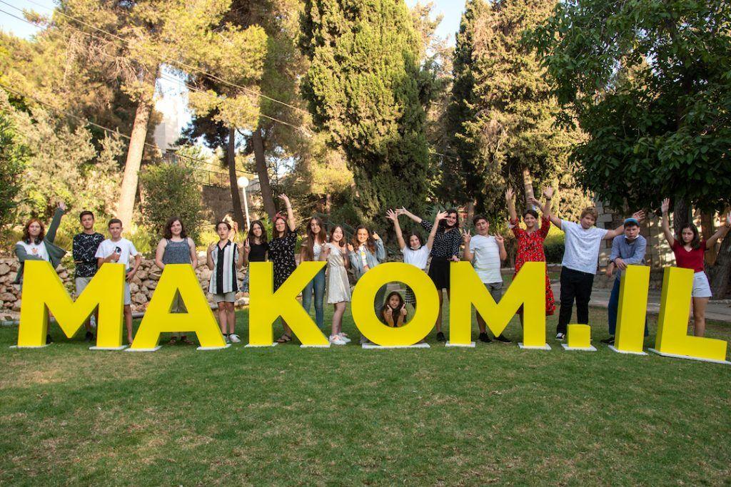ילדים עומדים בשורה מאחורי שלט Makom.IL